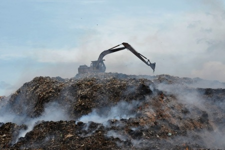 landfill excavator work on fire and smoke